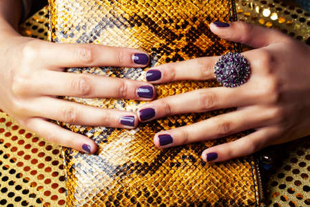 pretty fingers of african american woman holding money closeup with purse, luxury jewellery on python clutch, cash for gifts