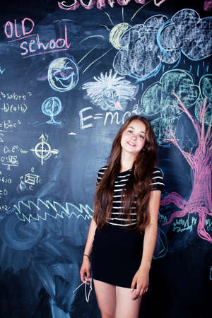 young cute teenage girl in classroom at blackboard cheerful smiling, lifestyle modern people concept
