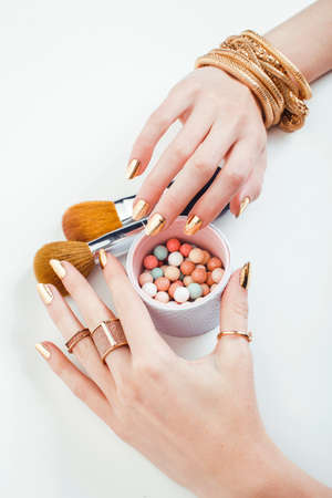 woman hands with golden manicure and many rings holding brushes, makeup artist stuff stylish, pure closeup pink flower rose among cosmetic for makeup Zdjęcie Seryjne