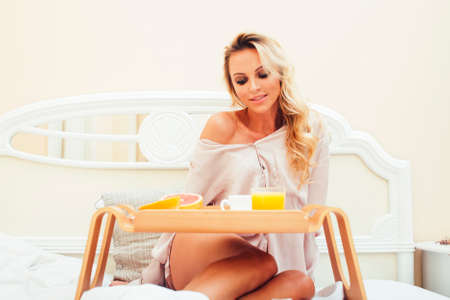 young beauty blond woman having breakfast in bed early sunny morning, princess house interior room, healthy lifestyle concept Stock Photo