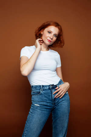young pretty redhead girl posing cheerful on warm brown background, lifestyle people concept