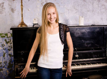 pretty young blond real girl at piano in old-style rusted interior, vintage concept