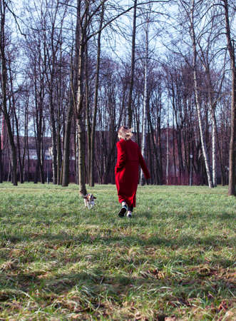 pretty young girl in redd coat playing with dog outside in green park, lifestyle people concept Stok Fotoğraf