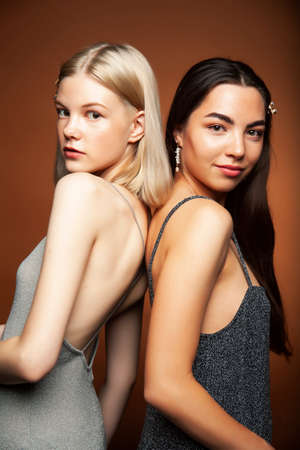 two pretty diverse girls happy posing together: blond and brunette on brown background, lifestyle people concept