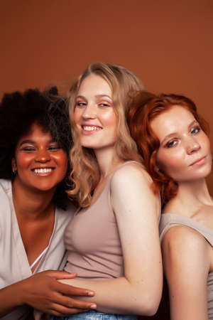 young pretty caucasian, afro, scandinavian woman posing cheerful together on brown background, lifestyle diverse nationality people concept