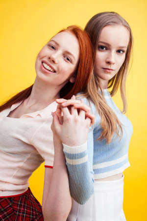 lifestyle people concept: two pretty young school teenage girls having fun happy smiling on yellow background