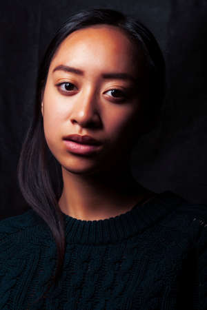 pretty young asian girl posing sensitive on black background, lifestyle people concept