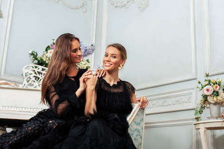 two young pretty lady in black lace fashion style dress posing in rich interior of royal hotel room, luxury lifestyle people concept