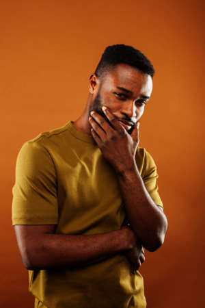 young pretty african american man posing cheerful on brown background, lifestyle people concept