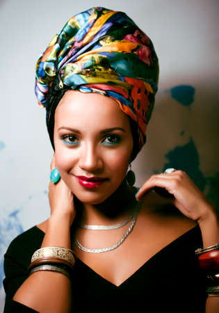 beauty bright african woman with creative make up, shawl on head like cubian closeup smiling Foto de archivo