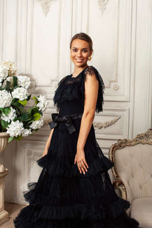 young pretty lady in black lace fashion style dress posing in rich interior of royal hotel room, luxury lifestyle people concept