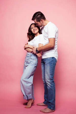 young cheerful caucasian couple together having fun on pink background, guy ang girl modern relationship, lifestyle people concept