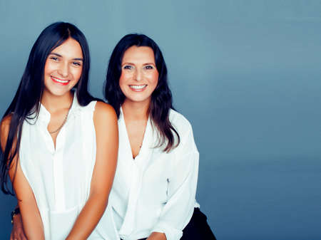cute pretty teen daughter with mature mother hugging, fashion style brunette, lifestyle people concept