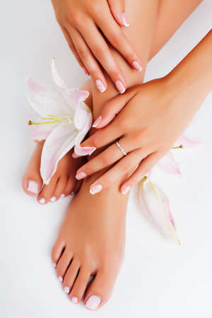 manicure pedicure with flower lily closeup isolated on white perfect shape hands spa salon Stockfoto