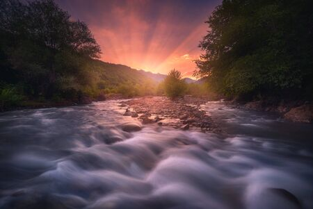 Magic sunrise over fast flowing mountain river