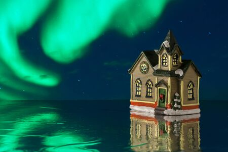 Beautiful creative winter composition. Christmas Story. Small toy house. Aurora background. Close up