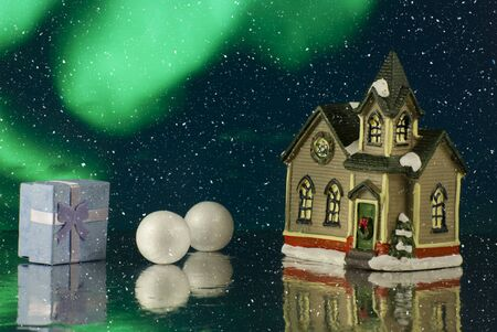 Beautiful creative winter composition. Christmas Story. Small toy house with gift or present box. magical background. Close up Stock Photo