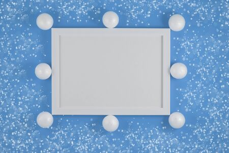 White frame and christmas decoration on blue background. Flat lay. Party mockup. Invitation or greeting card