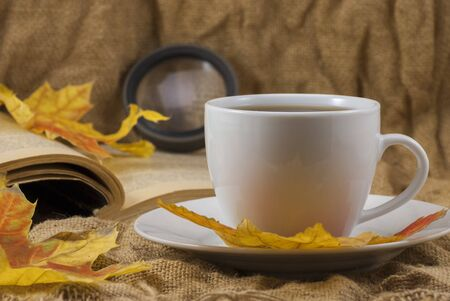 Autumn composition. Cup of coffee with book on autumn background. Autumn elegant concept. Close up