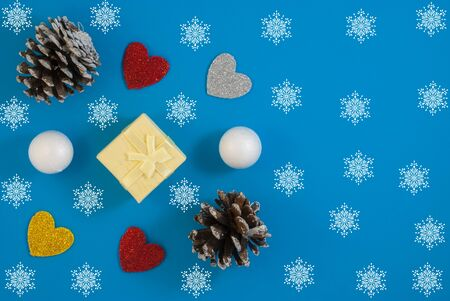 Christmas background with beautiful gift or present box, snowy pine cones and decorative snowballs, holiday. Top view