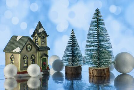 Christmas composition with Christmas tree, small toy house and decorative snowballs against holiday lights background