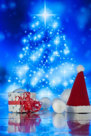 Christmas composition with Santa claus cap, gift or present box and decorative snowballs against holiday lights background Zdjęcie Seryjne