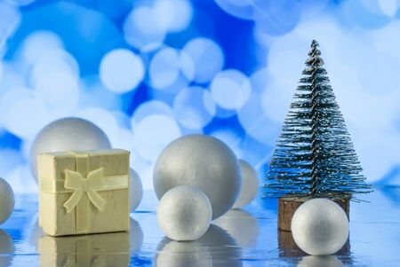 Beautiful Christmas composition with Christmas tree, gift or present box and decorative snowballs against holiday lights background, Holiday greeting card