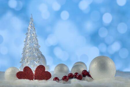 Piękna świąteczna kompozycja z choinką, sercami i ozdobnymi śnieżkami na tle światła świątecznego, kartka z życzeniami świątecznymi
