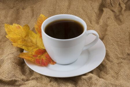 Autumn composition. Cup of coffee, dried leaves background. Autumn elegant concept. Close up Фото со стока