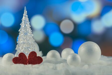 Beautiful Christmas composition with Christmas tree, Hearts and decorative snowballs against holiday lights background, Holiday greeting card