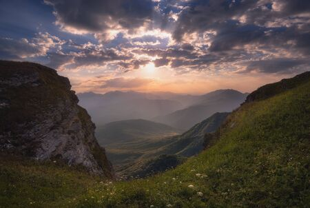 Summer sunrise landscape. Colorful summer sunrise with sun rays coloring the hills Stock Photo - 138466772