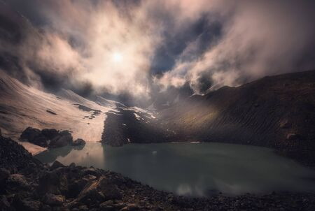 Beautiful misty sunset over mountain lake and glacier. after rain