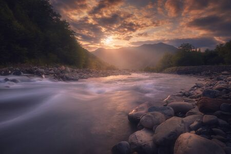Beautiful sunset over fast flowing mountain river. Caucasus Mountains. Racha