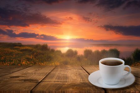 Coffee cup on wood table and view of beautiful sunset or sunrise background Banque d'images