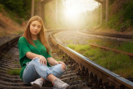 Young beautiful model posing on a railroad tracks