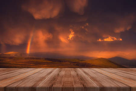 The Sky With beauriful Clouds And A Rainbow After The Rain with empty wooden table. Natural template landscape.