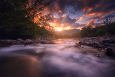Beautiful sunny summer landscape. Sunset over fast flowing mountain river.