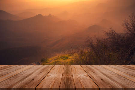 Autumn beautiful background with sunset over mountains and empty wooden table in nature outdoor. Natural template landscape. Фото со стока