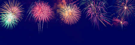 Colorful fireworks with wide blue copy space.