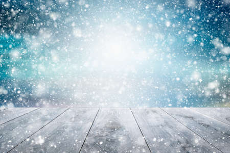 Winter snow background, beautiful light and snow flakes with empty wooden table. copy space.