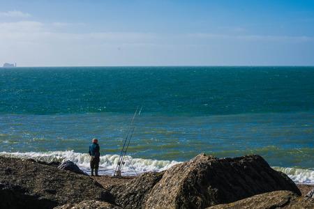 angler: Sea angler fisherman attending to his rods