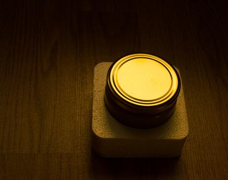 gloving up: Illuminated jar lid in dark background