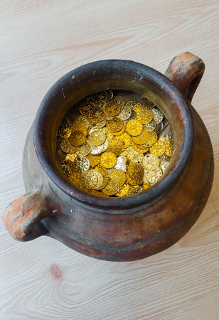 silver coins: Fake gold and silver coins in earthenware jar Stock Photo