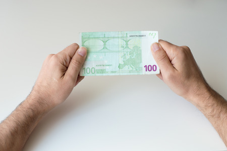 one hundred euro banknote: Man holding one hundred Euro banknote in his hands Stock Photo
