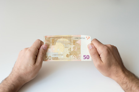 fifty euro banknote: Man holding fifty  Euro banknote in his hands Stock Photo
