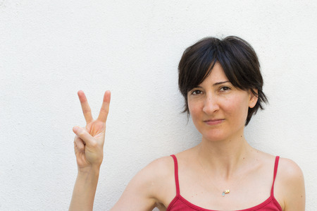 Young Woman Making Peace Sign in Front of a Wall Stock Photo