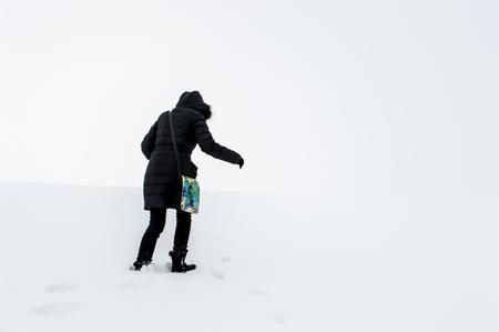 snowy field: Woman in black walking in a snowy field