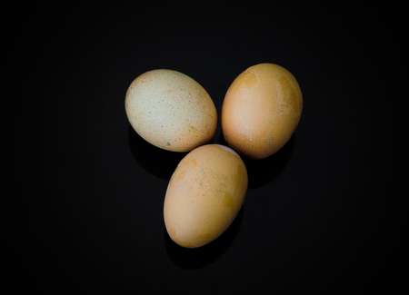 gamme de produit: Three eggs with shell on a black background Banque d'images