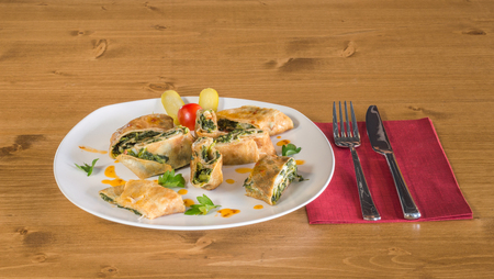 filled roll: Delicious wrapped crepe with spinach and pickles beside served on a white plate  on a wooden table with fork and knife on a red napkin Stock Photo