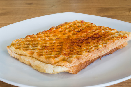 Closeup of Turkish toast, toasted sandwich with cheddar cheese served on a white plate on a wooden table